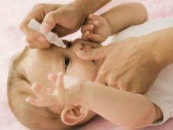 Закапывание препарата в глаза младенцу