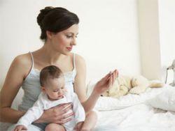 Женщина с младенцем измеряет температуру тела