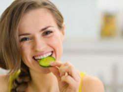 Женщина ест огурцы