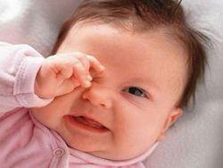 Младенец трет глаз рукой