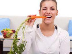 Женщина ест морковь
