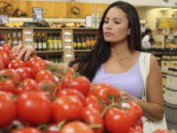Женщина выбирает помидоры