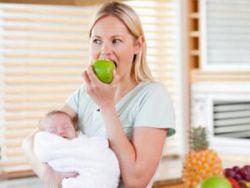 Мама с ребенком на руках ест яблоко
