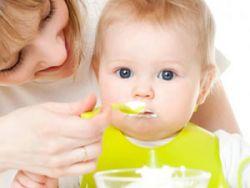 Ребенка кормят творожком