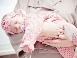 Новорожденная девочка в вязаной одежде